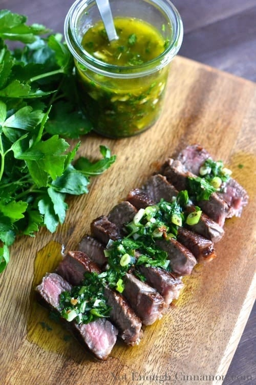 Sliced Sirloin Steak with Chimichurri Sauce served on a wooden chopping board with a small glass dish with chimichurri sauce on the side