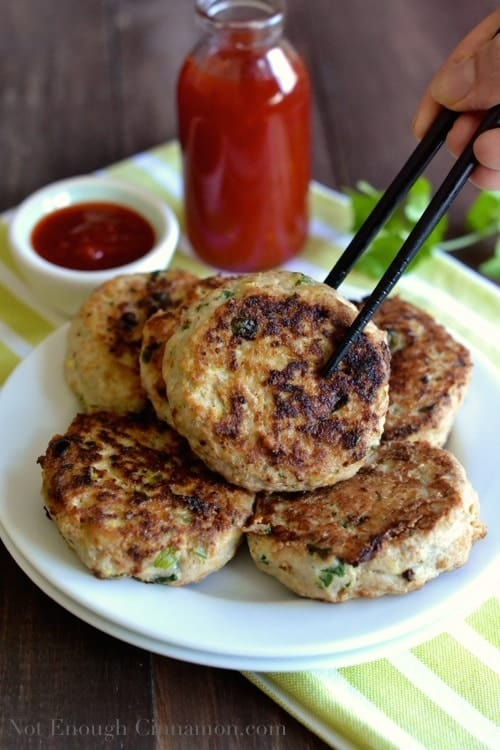 a pan-fried Paleo Thai Chicken Pattie on a plate with more patties being picked up with chopsticks - chicken patties recipe