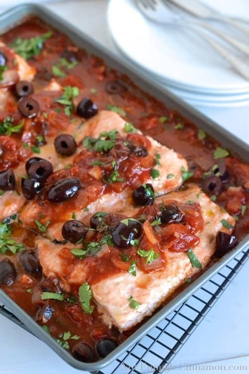 Oven Baked Salmon in a rich tomato olive Provencal Sauce served in a casserole dish with some plates in the background