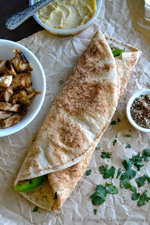 a big Grilled Chicken and Hummus Wrap lying on a piece of crinkled parchment paper surrounded by side dishes with hummus, chicken and za'atar spice