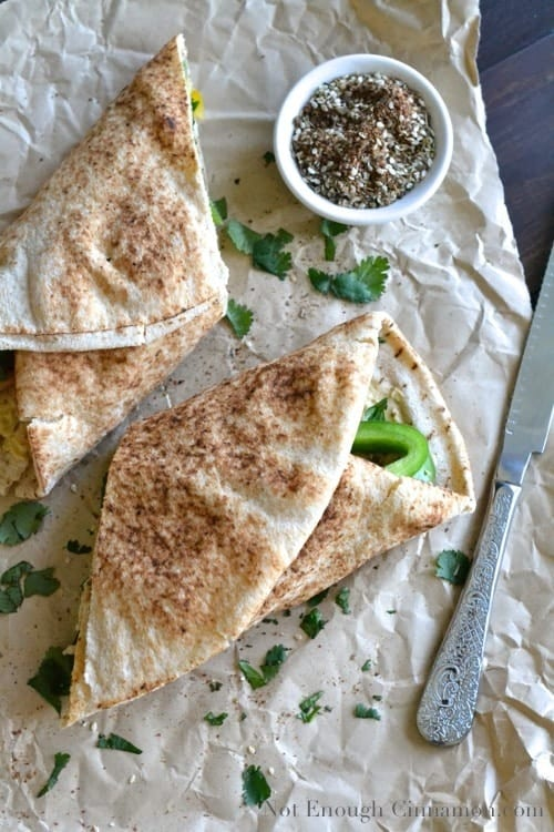 Grilled Chicken and Hummus Wraps on a crinkled piece of parchment paper sprinkled with fresh cilantro leaves, and a small dish with za'atar spice on the side