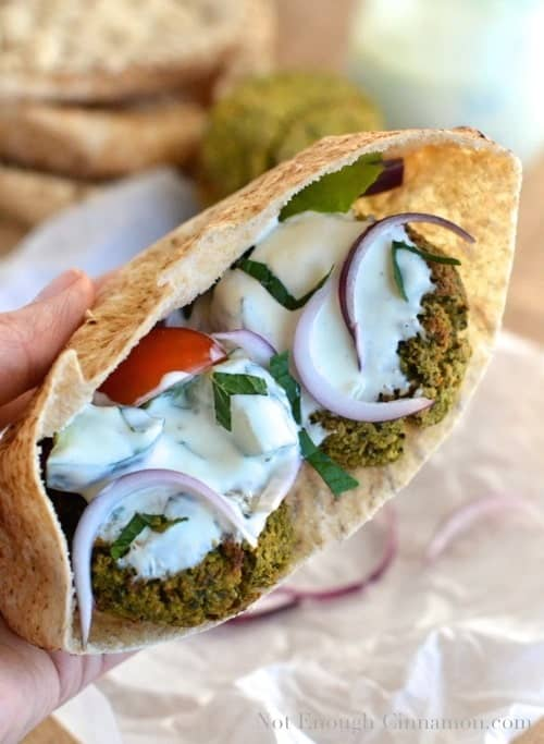 a hand holding a Baked Falafel Pita Sandwich stuffed with oven baked falafel, tomatoes, onions and a mint cucumber yogurt sauce