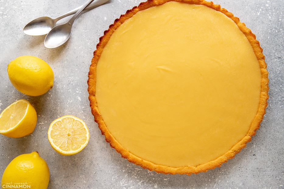 Whole paleo lemon curd tart with lemons and silver spoons on the side.