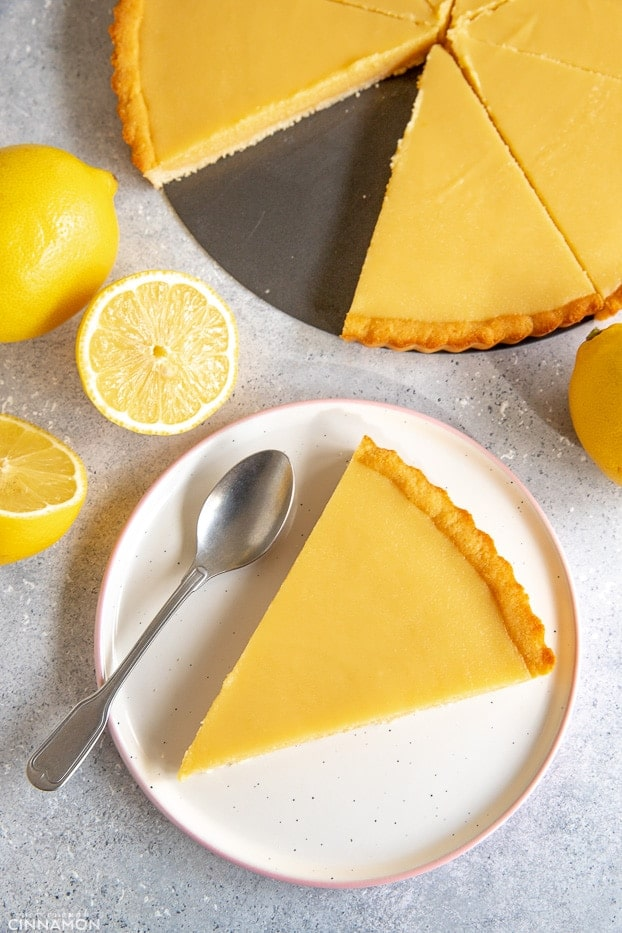 A slice of paleo lemon tart in a plate with a silver spoon and the whole tart sliced