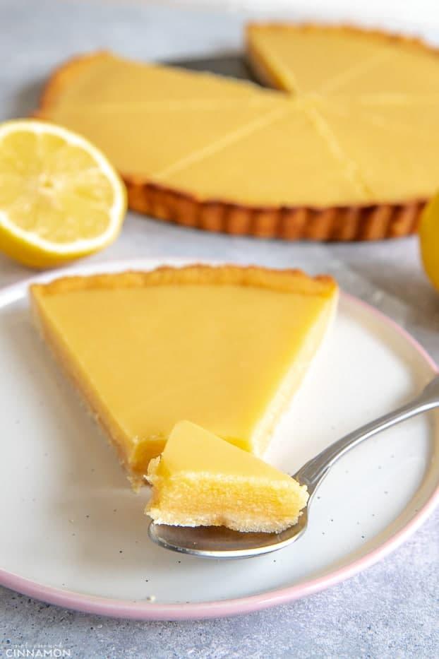 A piece of lemon curd tart in a silver spoon next to its slice.