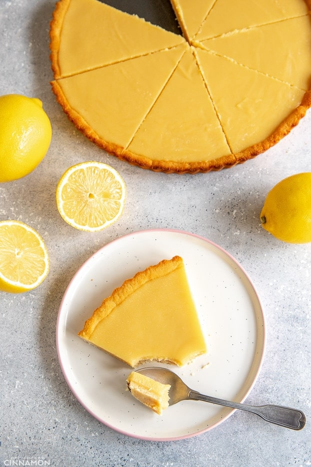 Paleo lemon curd tart with a slice on a white plate