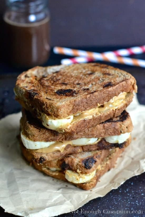 a stack of Peanut Butter and Banana Sandwiches with a jar of homemade peanut butter chocolate sauce and some straws in the background