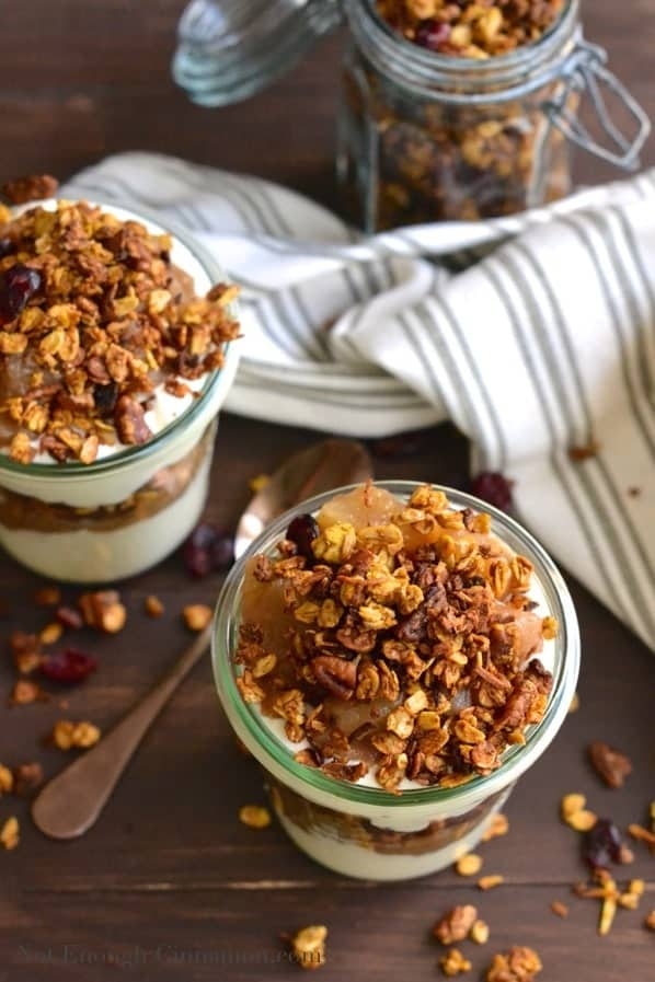 overhead shot of 2 Pumpkin Granola and Apple Yogurt Parfaits on a rustic wooden tabletop with a jar with homemade granola in the background