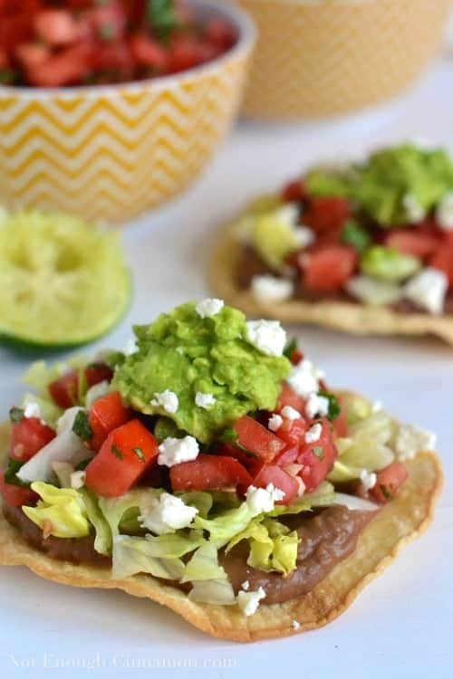 side view of Vegetarian Baked Tostadas topped with refried beans, homemade pico de gallo and creamy mashed avocado