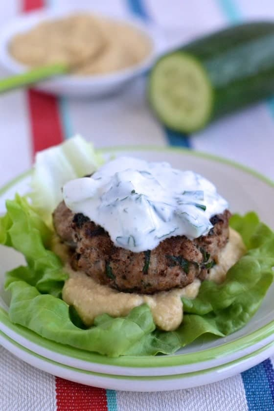 Middle Eastern Lamb Burger patties served on a lettuce leave with hummus and homemade tzatziki
