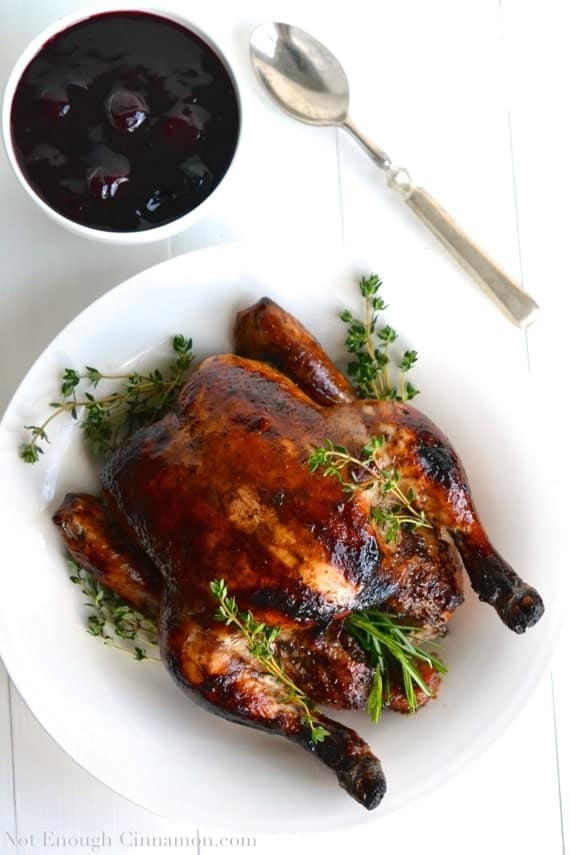 Balsamic marinated Roasted Chicken with perfect crispy sking served on a white platter with a side dish of homemade Easy Cherry Sauce in the background