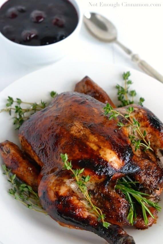 Balsamic Roasted Chicken served on a white platter with a small side dish of Easy Cherry Sauce in the background