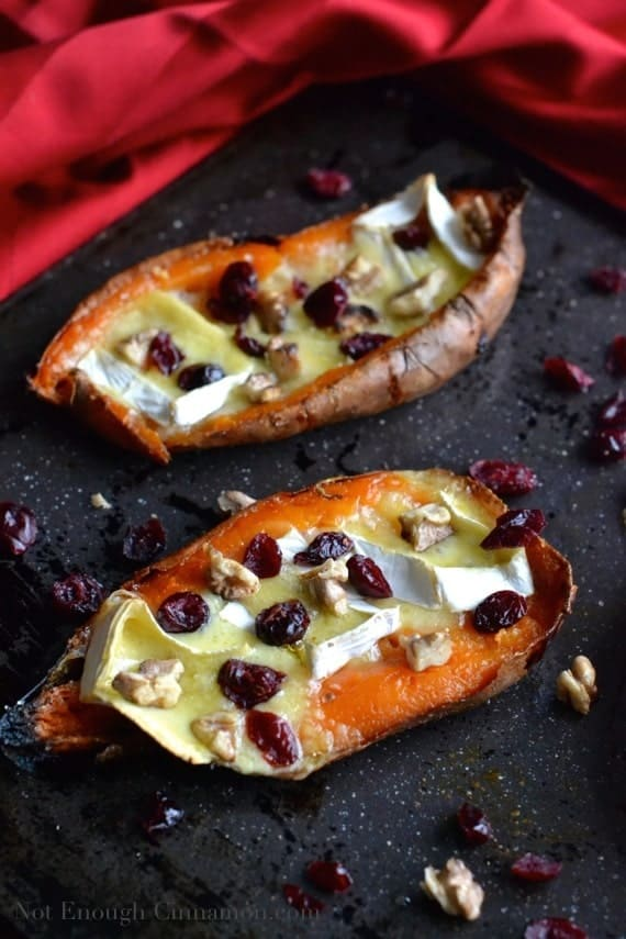 two Baked Sweet Potato Skins stuffed with brie and cranberries, served on a black tray with some dried cranberries surrounding them