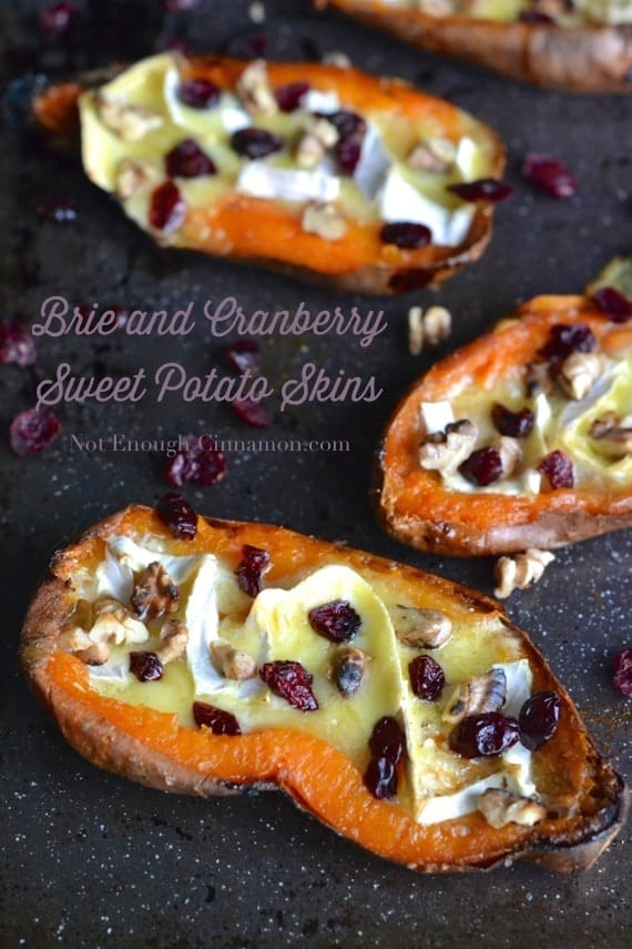 Brie and Cranberry Sweet Potato Skins arranged on a black tray with some dried cranberries surrounding them