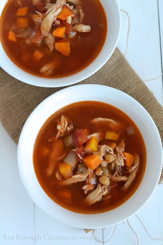 overhead shot of  Chicken Minestrone Soup with shredded chicken and vegetable cubes in a tomato broth