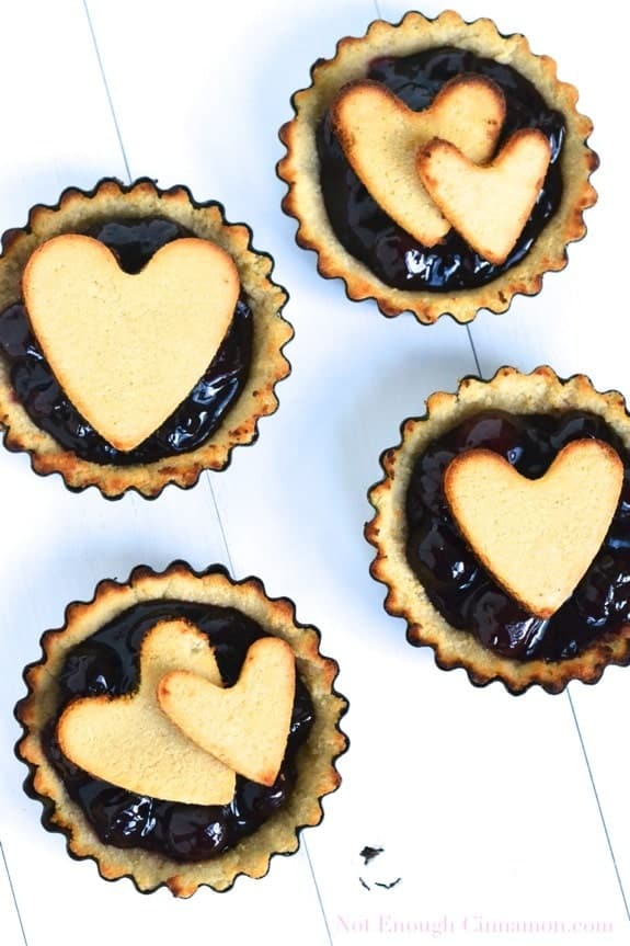 overhead shot of four mini tart molds of Paleo Cherry Pie