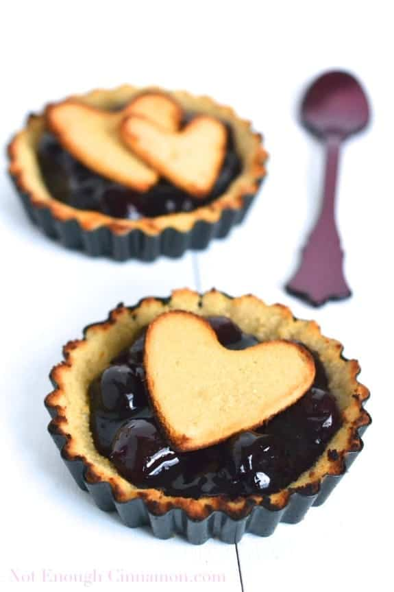 two mini tarts of Paleo Cherry Pie decorated with heart-shaped pie dough cut outs