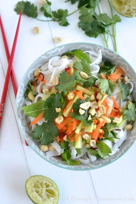 a bowl of Vietnamese Noodle Salad tossed with Tahini Dressing and topped with chopped peanuts, with red chopsticks on the side