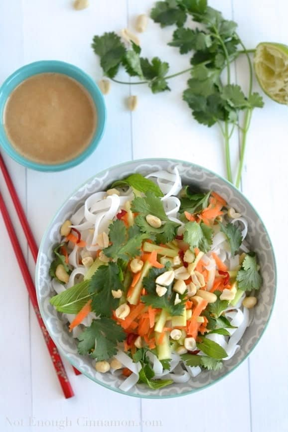a bowl of Vietnamese Noodle Salad on a white tabletop with a small dish with tahini dressing and some fresh cilantro in the background
