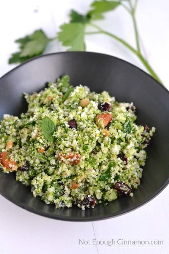 close-up of a black bowl of grain-free broccoli cauliflower tabbouleh studded with almonds and cranberries and garnished with fresh mint leaves