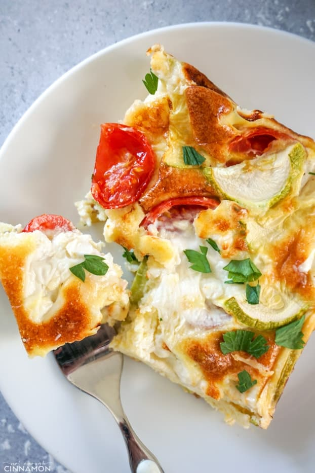 A piece of baked frittata in a white plate with a fork