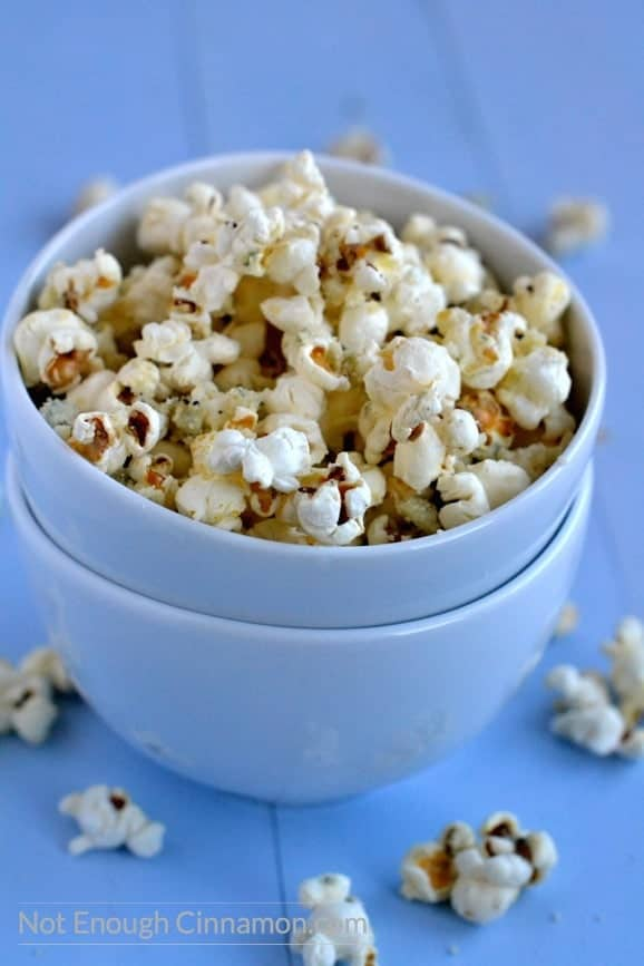 Homemade stovetop popcorn sprinkled with blue cheese and parmesan served in a blue bowl on a rustic blue table