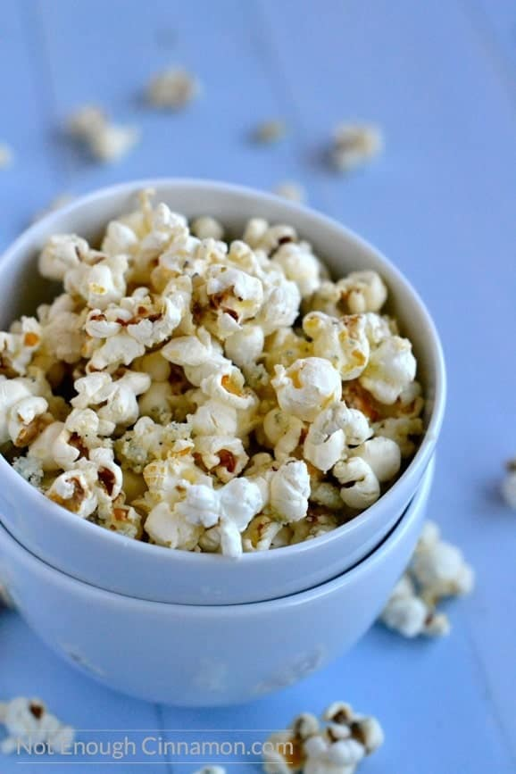 Homemade savory parmesan popcorn sprinkled with blue cheese served in a blue bowl stacked onto another bowl