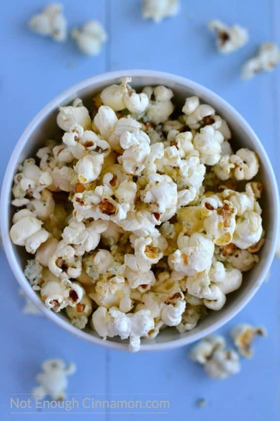 overhead shot of Homemade parmesan popcorn sprinkled with blue cheese served in a blue bowl
