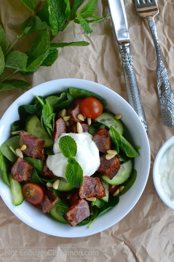 overhead shot of a bowl of Mediterranean Lamb and Spinach Salad topped with yogurt dressing, with some fresh mint and cutlery in the background