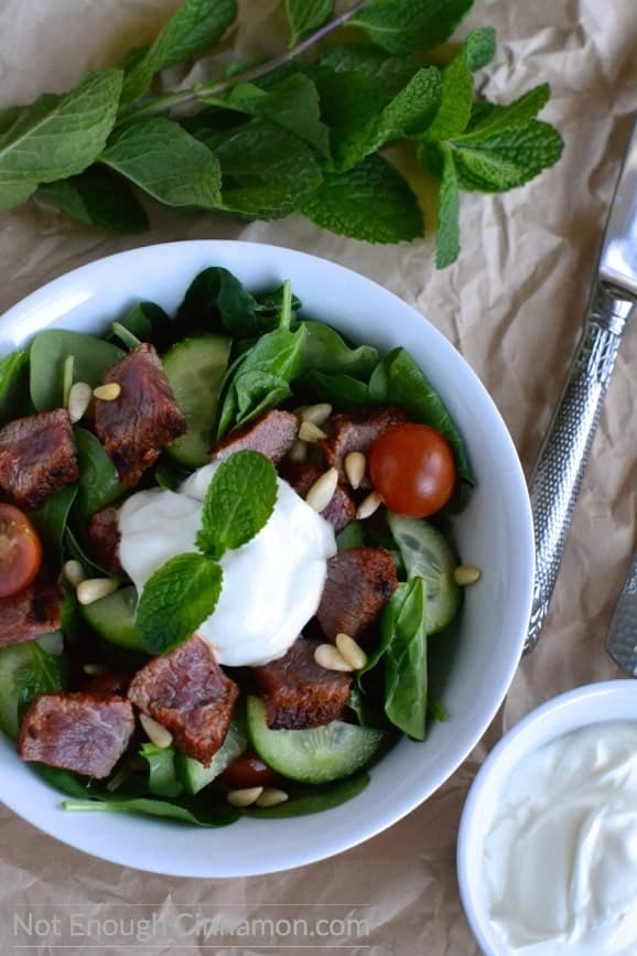 Mediterranean Lamb Salad with spinach, tomatoes, cucumbers and pine nuts served with a dollop of Greek yogurt dressing in a white salad bowl