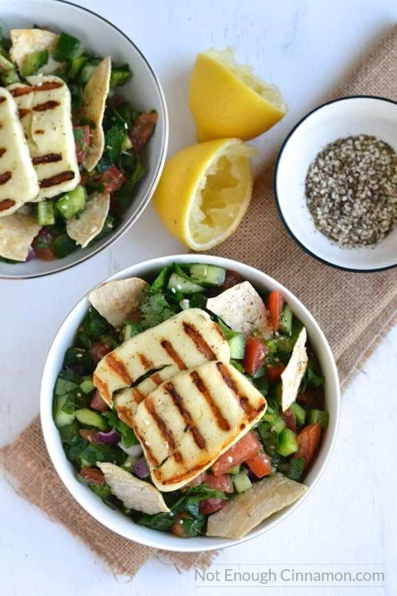 overhead shot of 2 bowls of fattoush salad topped with grilled halloumi cheese and tortilla chips with some lemons and seasoning on the side
