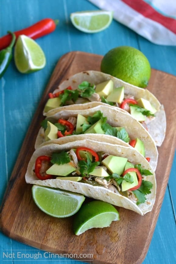 overhead shot of gluten-free Shredded Chicken Tacos lined up on a wooden board with some lime wedges on the side