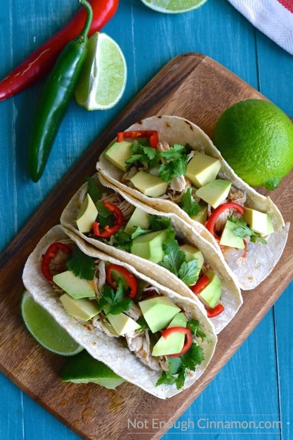 overhead shot of Healthy Shredded Chicken Tacos on a wooden board topped with avocado, sliced red chilies and fresh cilantro