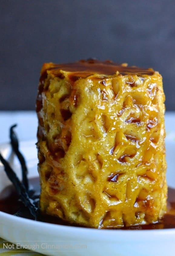 a whole Honey Roasted Pineapple on a plate glistening with Honey and Salted Butter Caramel sauce