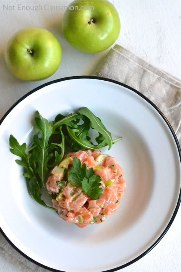 a serving of homemade salmon tartare with green apples and cilantro on a white plate with some arugula on the side and apples in the background