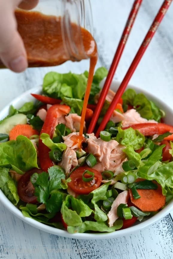Sweet Chili Sauce Dressing being poured on top of a Thai Salmon Salad in a white bowl