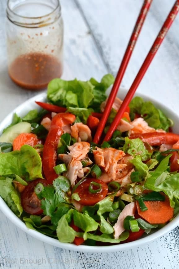 Thai Salmon Salad being tossed with Sweet Chili Sauce Dressing using chopsticks