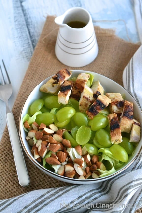 overhead shot of easy grilled chicken salad with grapes and almonds in a white bowl with a little dressing dispenser on the side