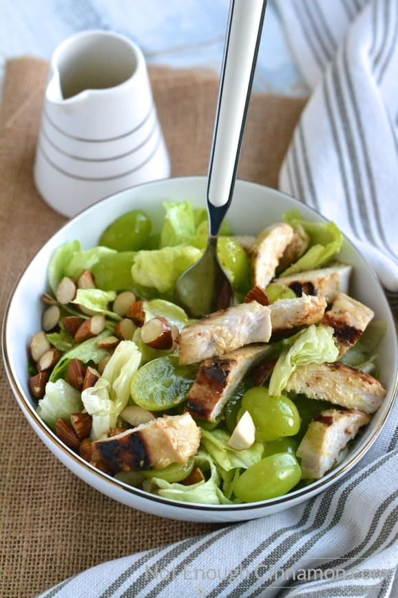 a fork in a bowl with chicken salad with grapes and almonds with a dressing dispenser on the side