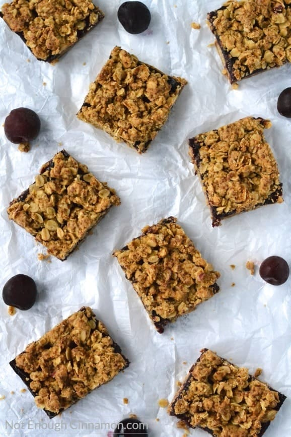 overhead shot of Healthy Cherry Oatmeal Bars with crunchy oat topping arranged on crinkled parchment paper with some fresh cherries