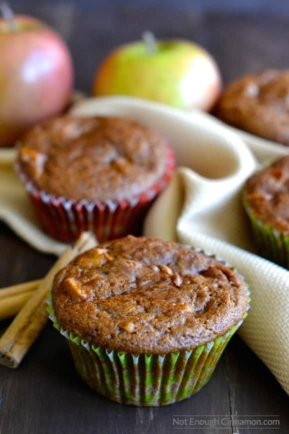 close-up of healthy apple spice muffin in a green muffin liner with more muffins and apples in the background