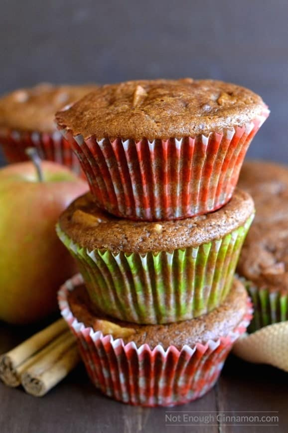 three healthy apple spice muffins stacked on top of each other with some apples and a cinnamon stick on the side