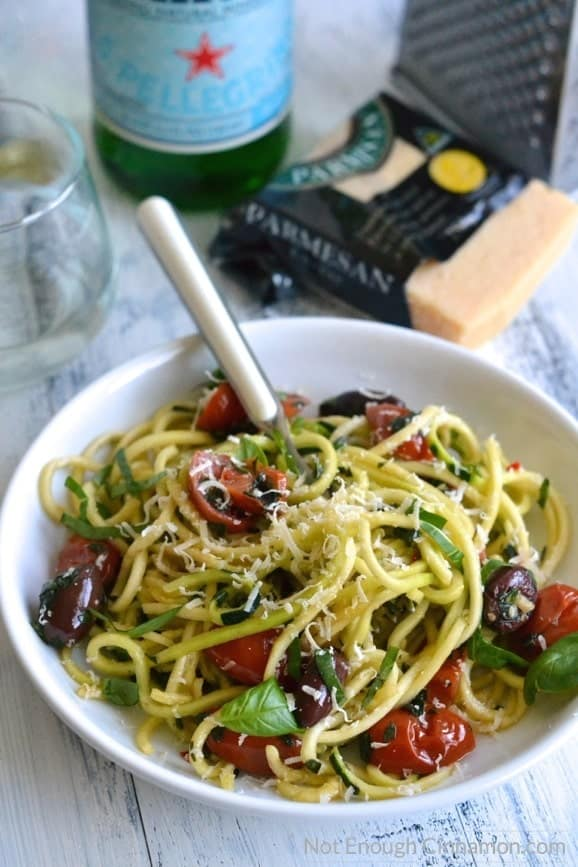 a fork twirling zucchini noodles alla puttanesca in a white bowl (zoodles recipe)