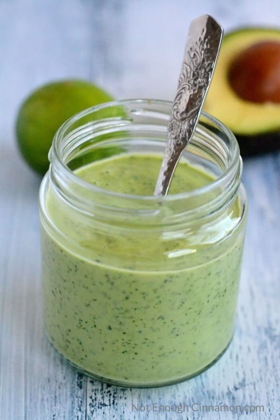 a mason jar with Creamy Cilantro Avocado Sauce on a rustic white table with an avocado and lime in the background