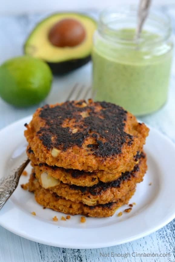 pan-fried Sweet Potato Quinoa Patties stacked on a white plate with a jar of Creamy Cilantro Avocado Sauce in the background