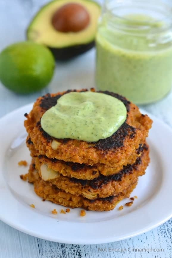 stacked Sweet Potato Quinoa Patties on a white plate topped with Creamy Cilantro Avocado Sauce