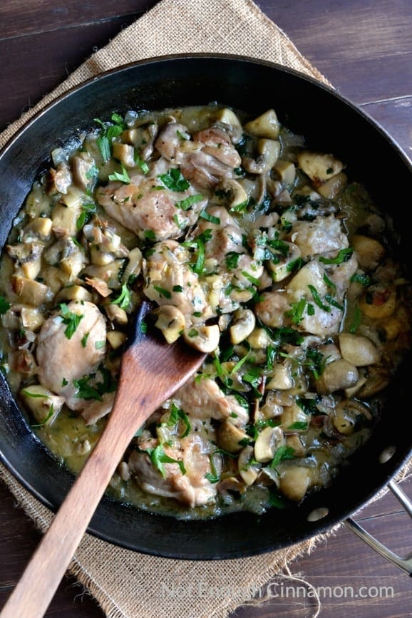 overhead shot of chicken with mushrooms sprinkled with fresh parsley and served in a black skillet on a rustic table