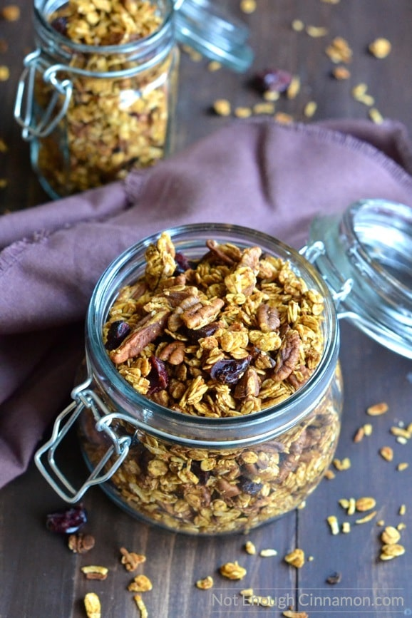 easy homemade pumpkin granola in two mason jars placed on a rustic wooden table with a purple napkin in the background