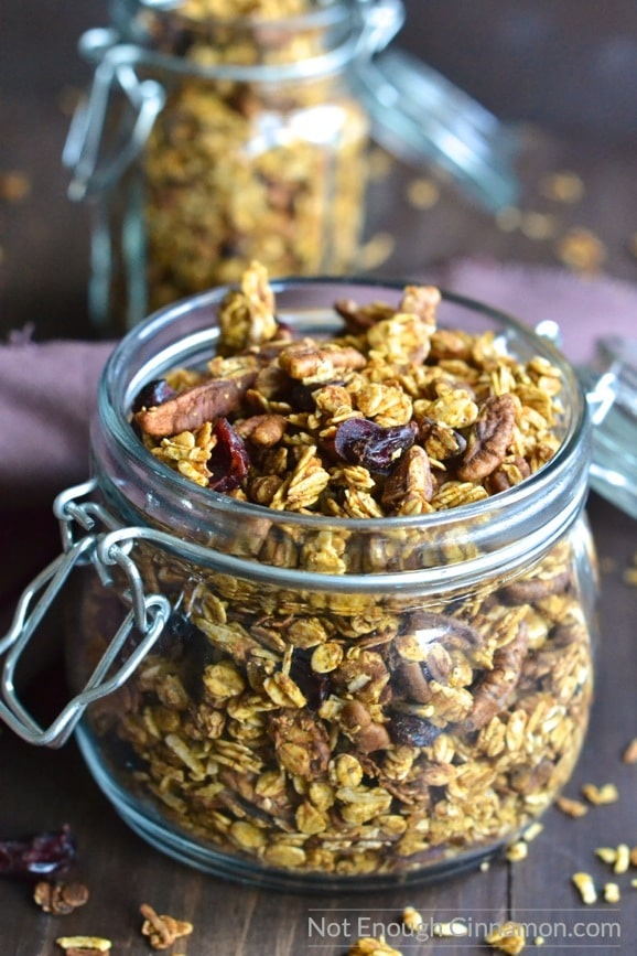 side view of a mason jar filled to the top with homemade pumpkin granola with some pecans and cranberries on top