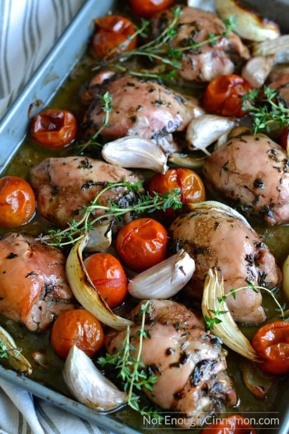 close-up of easy baked chicken thighs on a baking tray with thyme, blistered tomatoes and garlic nestled in between the tender thighs